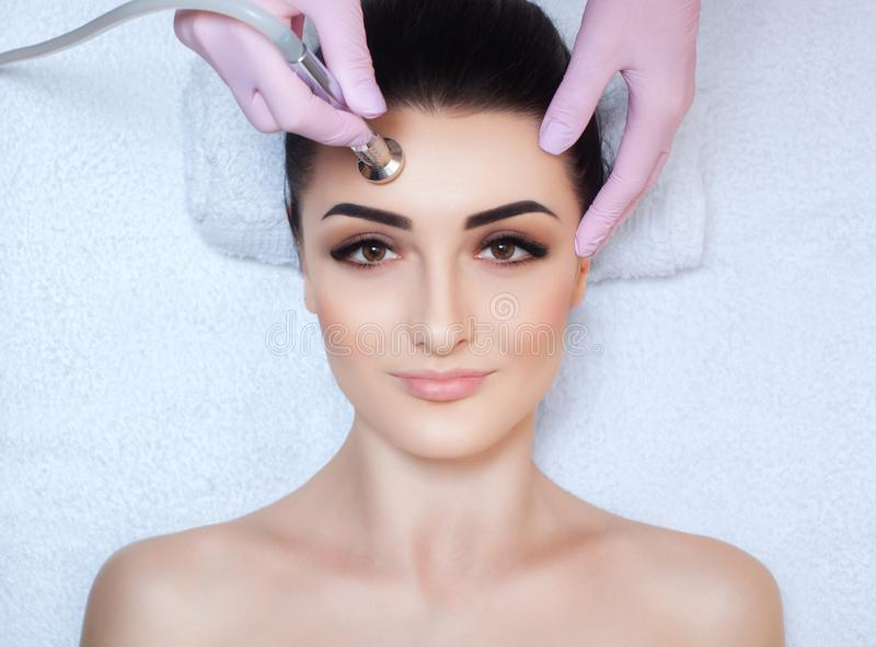 The cosmetologist makes the procedure Microdermabrasion of the facial skin of a beautiful, young woman in a beauty salon. royalty free stock photography