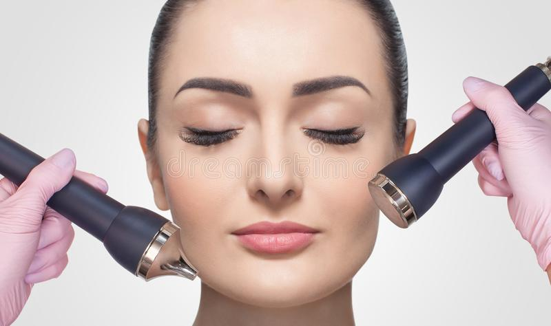 The cosmetologist makes the procedure an ultrasonic cleaning of the facial skin of a beautiful, young woman in a beauty salon royalty free stock photo