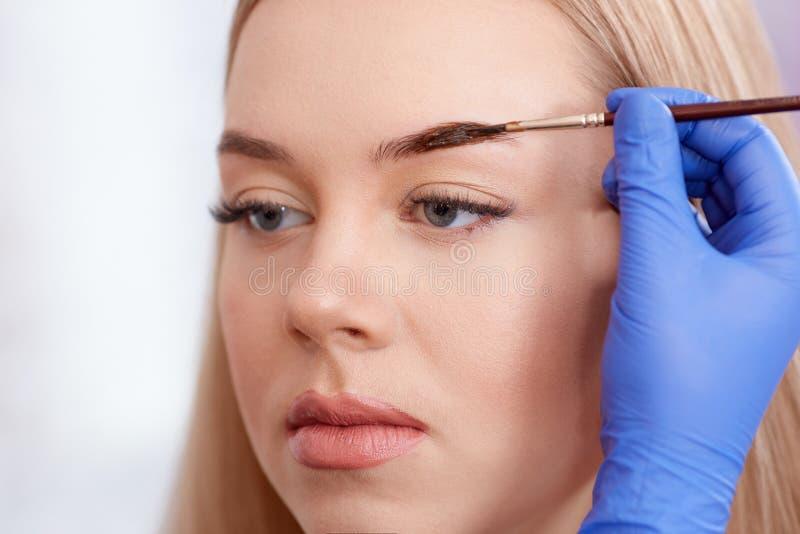Cosmetologist making permanent eyebrows using brush. stock photos