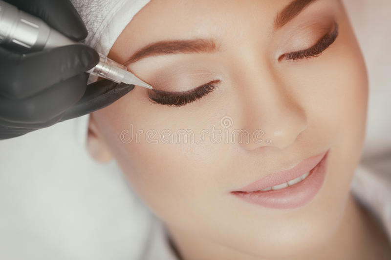 Cosmetologist making permanent make up at beauty salon royalty free stock photo