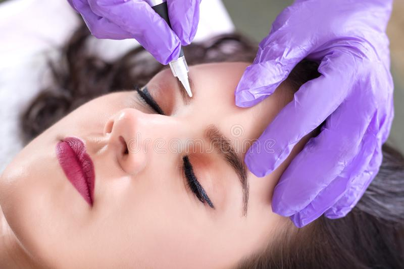 Cosmetologist making permanent make up on eyebrows stock photo