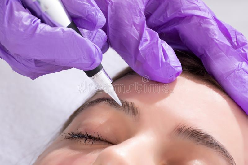 Cosmetologist making permanent make up on eyebrows on beautiful girl royalty free stock photo