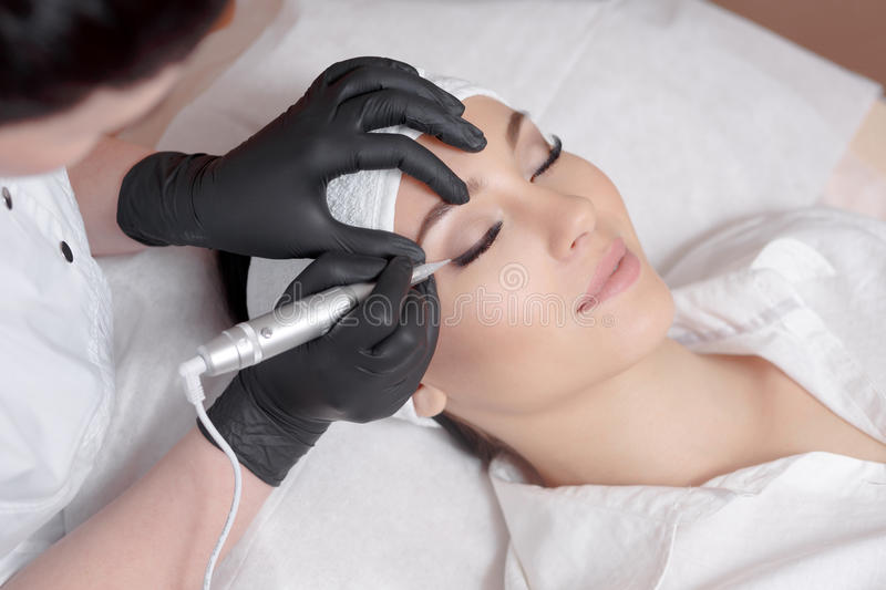 Cosmetologist making permanent makeup royalty free stock image