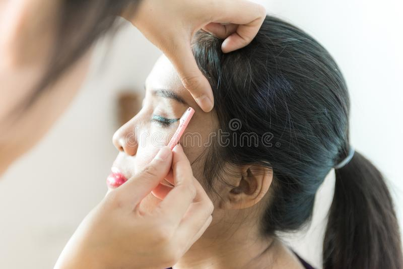 Cosmetologist making permanent makeup on face woman`s, woman plu royalty free stock image
