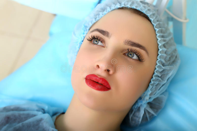Cosmetologist making permanent makeup on woman's face stock photos
