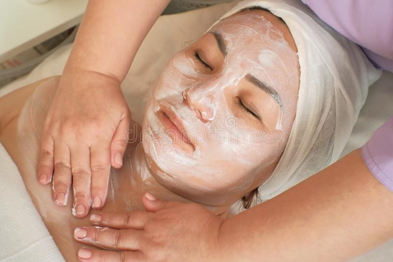 A cosmetologist massages a woman`s face and neck with a moisturizing mask. Close-up. Relaxed Asian woman takes beauty treatments royalty free stock photo
