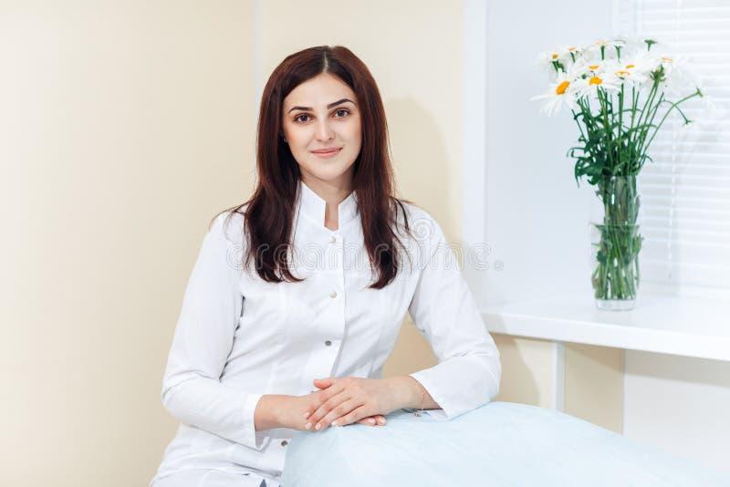 Cosmetologist moreno fêmea no uniforme perto da janela no escritório da cosmetologia fotos de stock