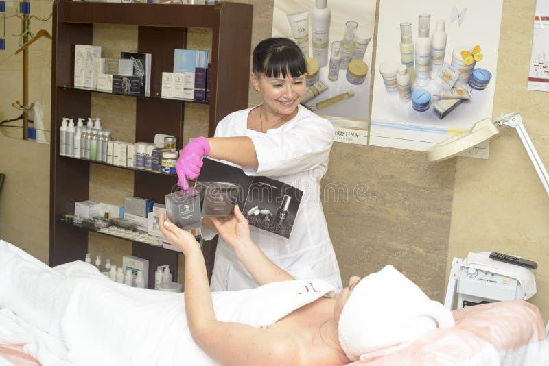 Cosmetologist oferuje klientów kosmetyki, Ukraina, Polyana wioska, Grudzień 2018 obraz royalty free