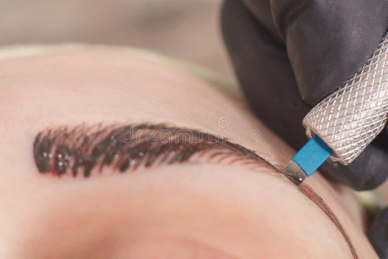 Cosmetologist permanent van toepassing zijn maakt omhoog op wenkbrauwen royalty-vrije stock foto