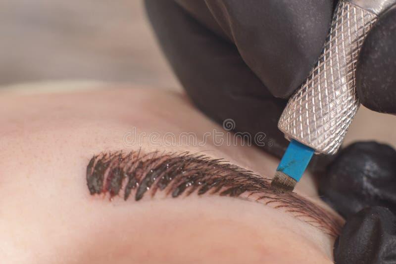 Cosmetologist permanent van toepassing zijn maakt omhoog op wenkbrauwen stock foto