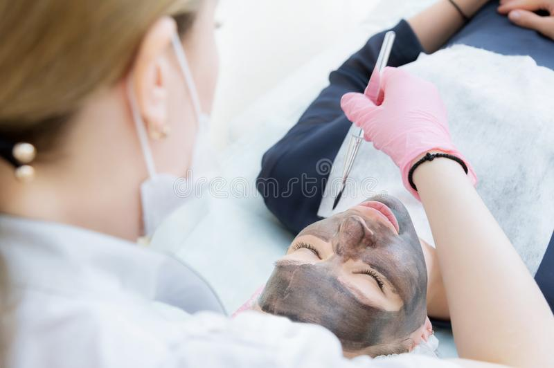The cosmetologist in pink gloves with a brush applies a carbon mask for peeling on the face of a young girl in a royalty free stock photos