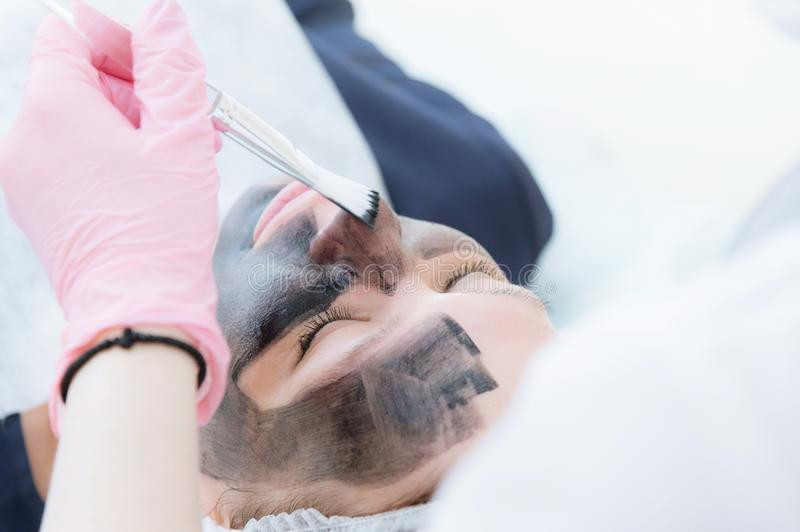 The cosmetologist in pink gloves with a brush applies a carbon mask for peeling on the face of a young girl in a stock photography