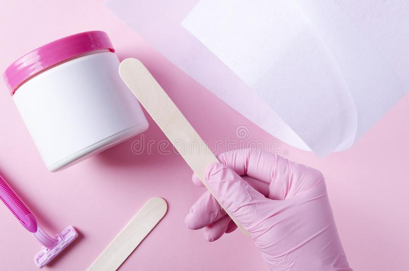 Cosmetologist in pink gloves taking stick to apply hot wax.Concept of hot waxing treatment.Top view of beauty waxing tools royalty free stock image