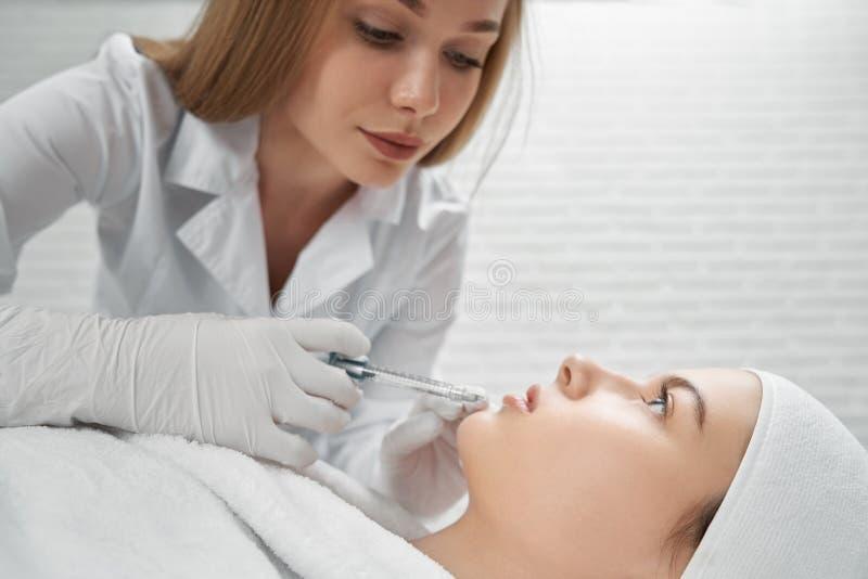 Cosmetologist pracuje kosmetyczne procedury i robi zdjęcie royalty free