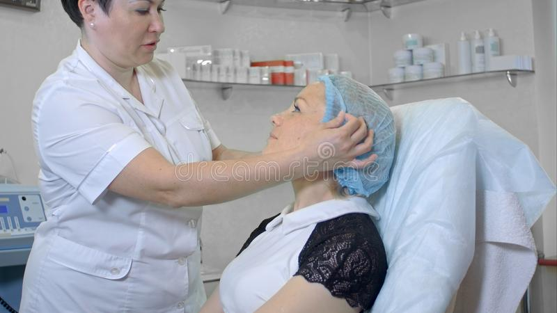 Cosmetologist preparing female client to a beauty procedure stock photos