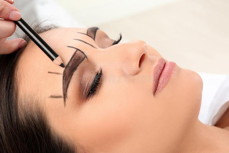 Cosmetologist preparing young woman royalty free stock image