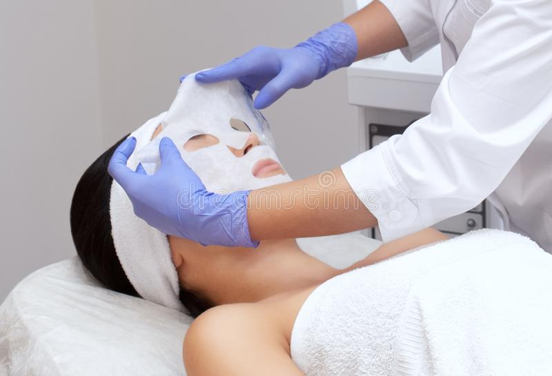 The cosmetologist for procedure of cleansing and moisturizing the skin, applying a sheet mask to the face. stock image