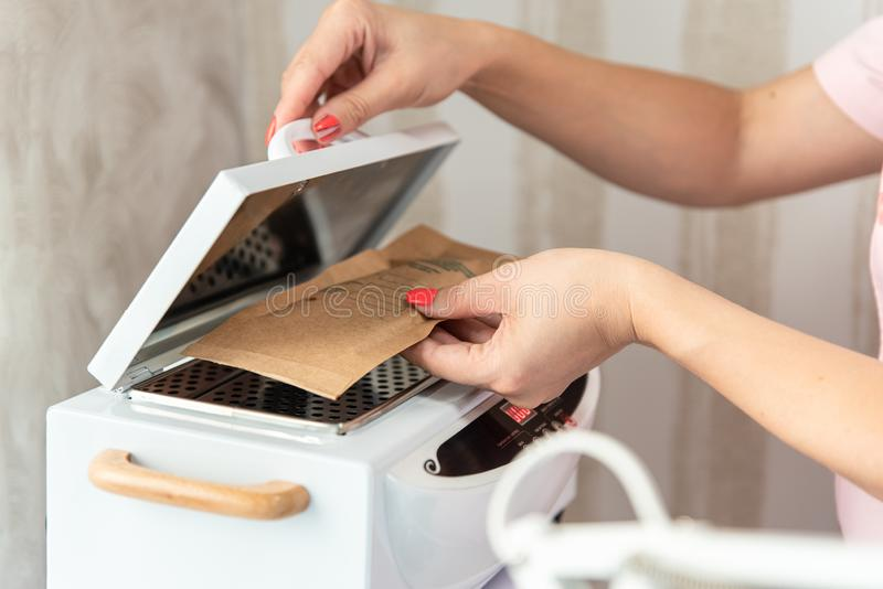 Cosmetologist puts the kraft bag with manicure tools in High Temperature Sterilizer. Cleanliness and disinfection. Beauty salon stock images
