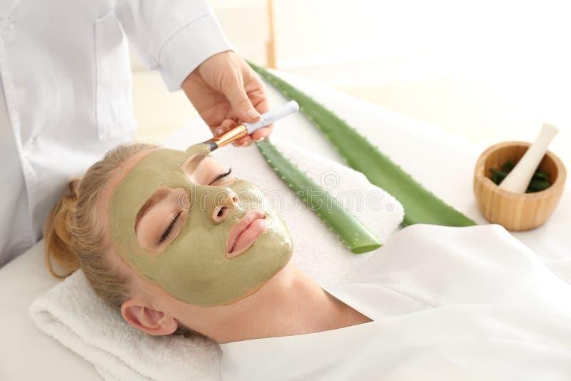 Cosmetologist que aplica la máscara con el extracto de Vera del áloe sobre cara de la mujer joven en salón de belleza fotografía de archivo libre de regalías