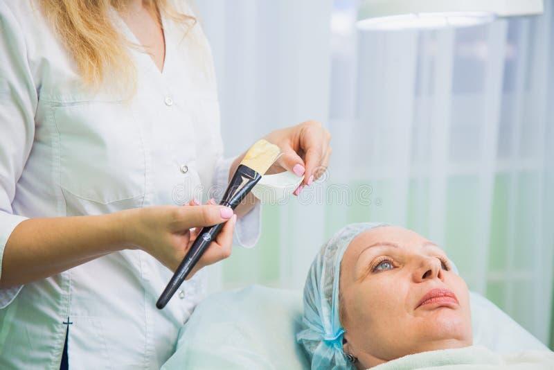 Cosmetologist que aplica la máscara en cara mayor de la mujer imagenes de archivo