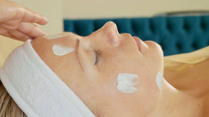 Cosmetologist que aplica a máscara de creme na cara da mulher bonita nova imagens de stock royalty free