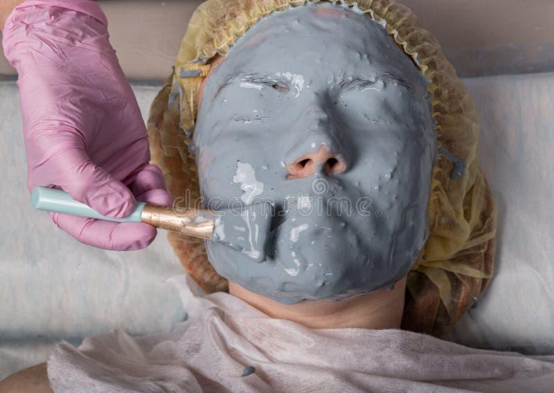 Cosmetologist que aplica a m?scara facial ? pele do problema jovem mulher que tem o procedimento de limpeza da cara imagem de stock