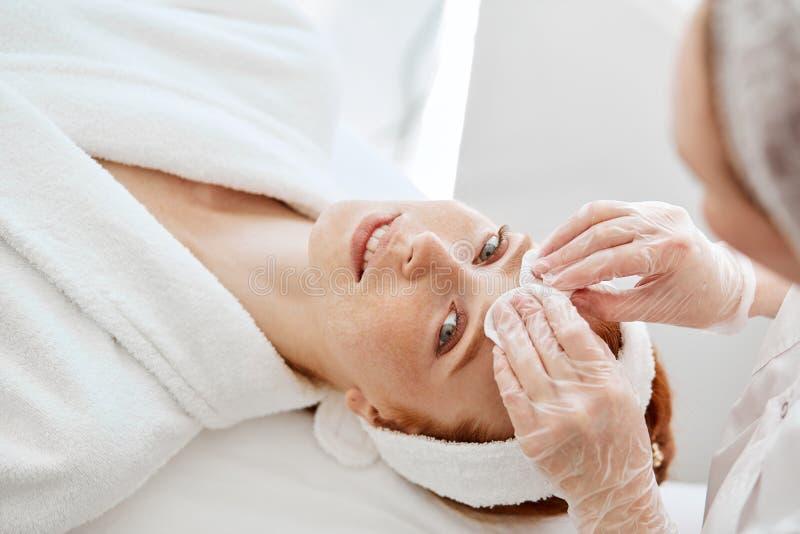 Cosmetologist que clinsing com a cara fêmea da almofada de algodão que prepara-se para o procedimento fotos de stock