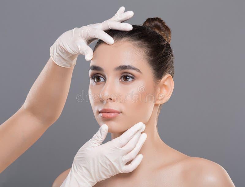 Cosmetologist que comprueba la cara de la mujer joven antes del tratamiento de la belleza fotos de archivo libres de regalías