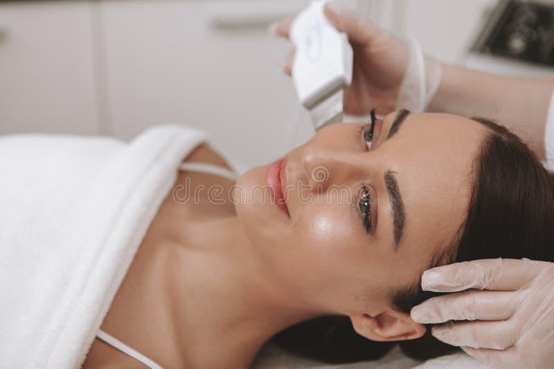 Cosmetologist que visita precioso de la mujer joven en la clínica de la belleza fotos de archivo