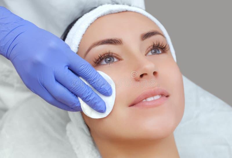 Cosmetologist reinigt met een tonicum de gezichtshuid van een mooie, jonge vrouw in een schoonheidssalon royalty-vrije stock foto