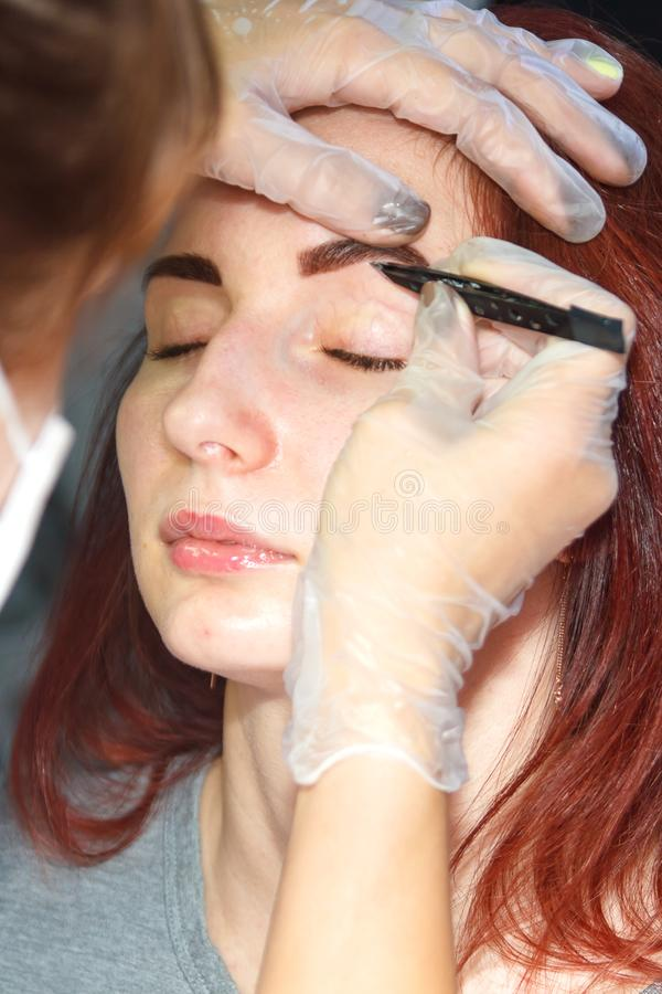 A cosmetologist removes excess eyebrow hairs to a client after staining with tweezers. royalty free stock photo