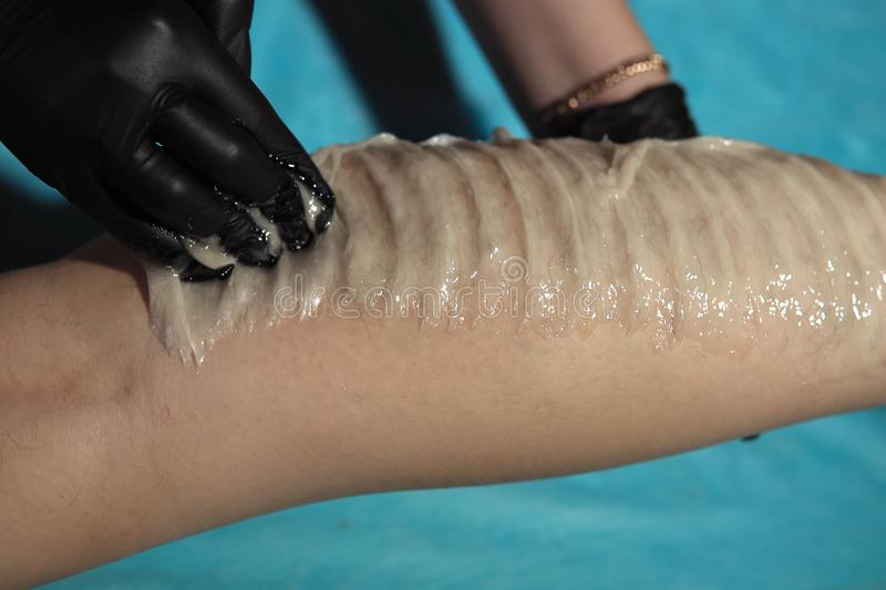 A cosmetologist removes hair from the legs of a young woman sugar paste royalty free stock image
