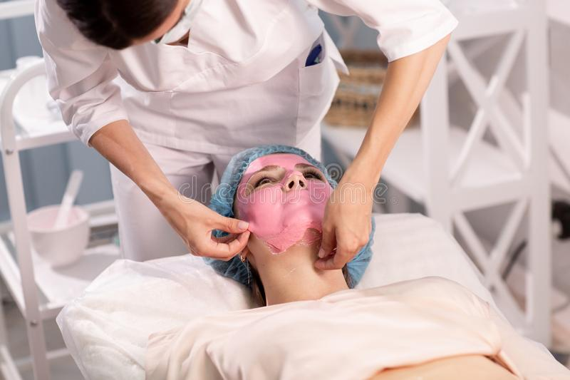 The cosmetologist removes the pink wellness mask from the patient`s face. Close up. Cosmetic procedures in the clinic stock photography