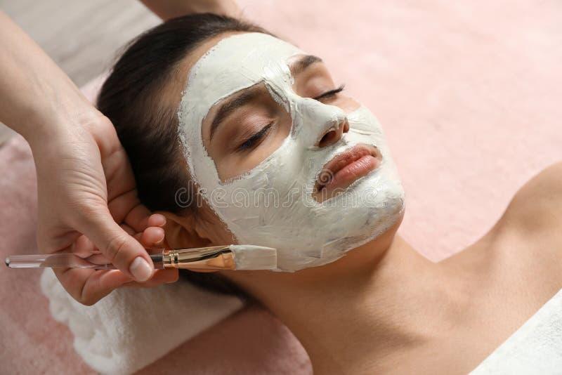 Cosmetologist som applicerar den vita maskeringen på kvinnas framsida royaltyfri bild