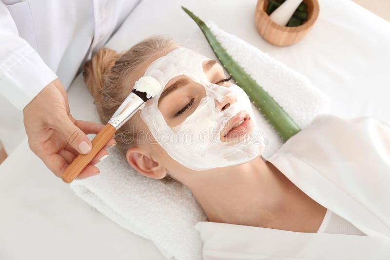 Cosmetologist som applicerar maskeringen med den aloevera extrakten på framsida av den unga kvinnan i skönhetsalong royaltyfria bilder