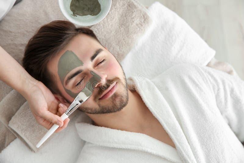 Cosmetologist som applicerar maskeringen p? klients framsida i brunnsortsalong, royaltyfri bild