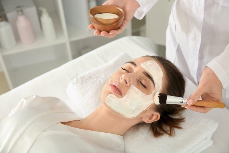 Cosmetologist som applicerar maskeringen p? framsida av den unga kvinnan i sk?nhetsalong royaltyfria foton