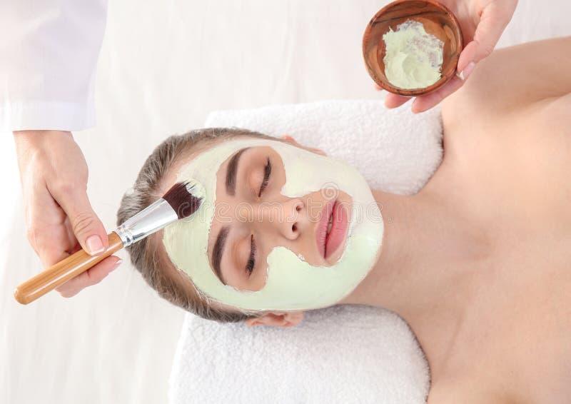 Cosmetologist som applicerar maskeringen p? framsida av den unga kvinnan i sk?nhetsalong royaltyfri fotografi