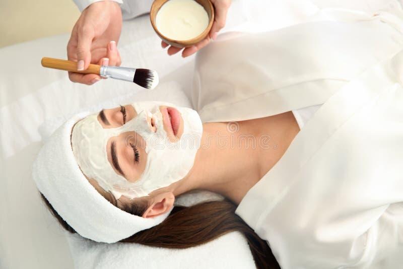 Cosmetologist som applicerar maskeringen p? framsida av den unga kvinnan i sk?nhetsalong royaltyfria bilder