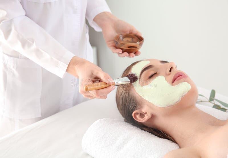 Cosmetologist som applicerar maskeringen p? framsida av den unga kvinnan i sk?nhetsalong arkivfoton