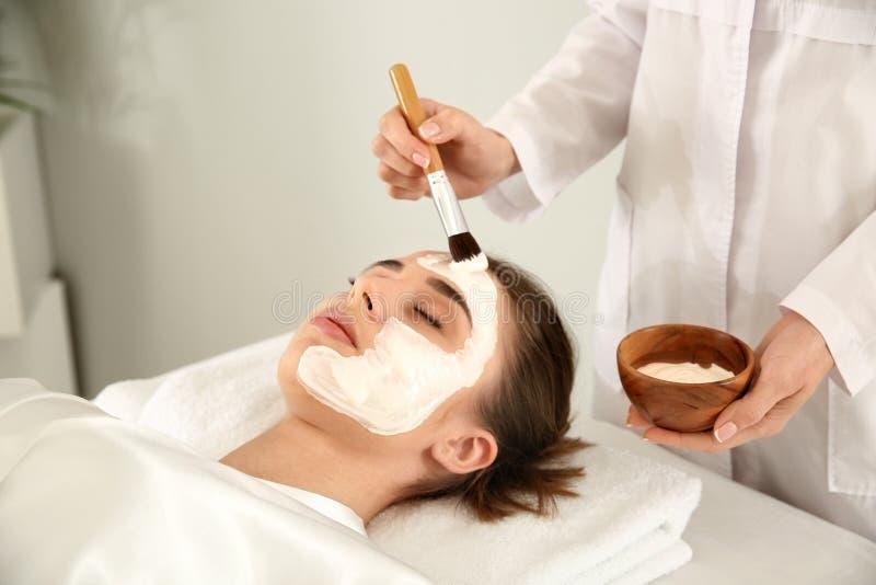 Cosmetologist som applicerar maskeringen p? framsida av den unga kvinnan i sk?nhetsalong arkivfoto