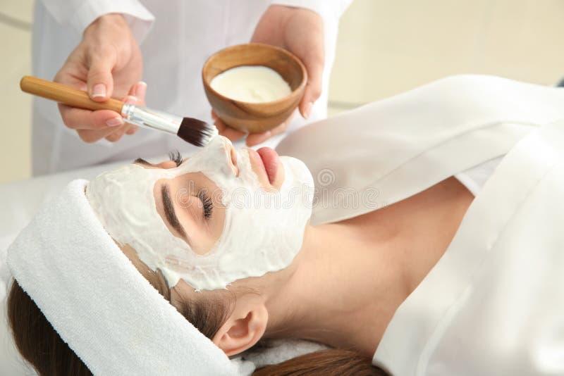 Cosmetologist som applicerar maskeringen p? framsida av den unga kvinnan i sk?nhetsalong royaltyfri foto