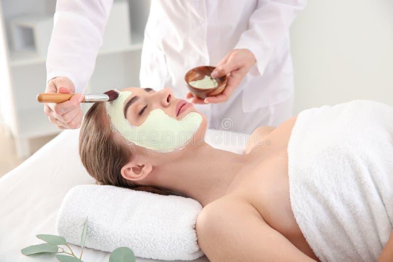 Cosmetologist som applicerar maskeringen p? framsida av den unga kvinnan i sk?nhetsalong arkivbilder