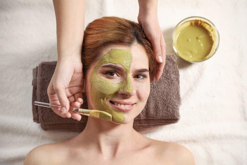 Cosmetologist som applicerar maskeringen p? kvinnas framsida, b?sta sikt royaltyfria bilder