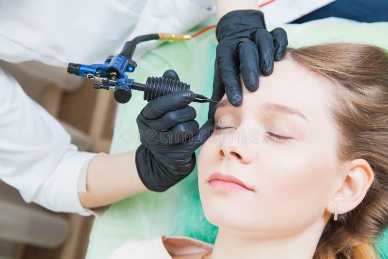 Cosmetologist som applicerar permanent makeup på krön royaltyfri fotografi