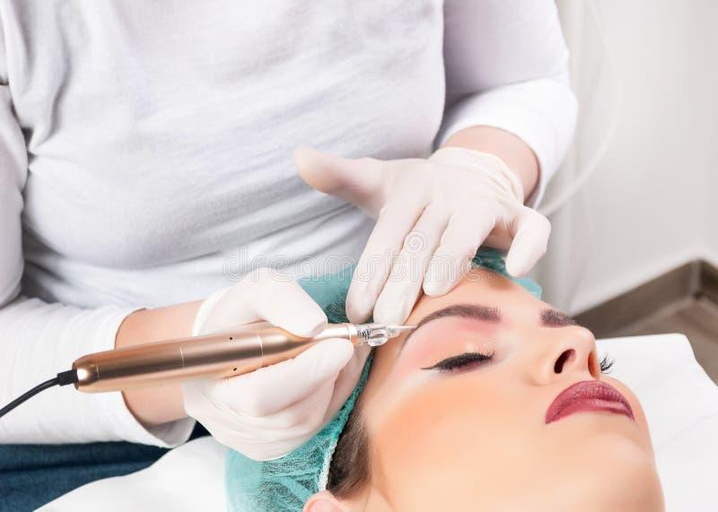 Cosmetologist som applicerar permanent smink på ögonbryn arkivbild
