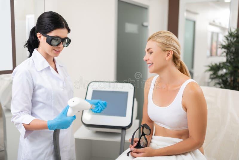 Cosmetologist som får klar till ansikts- föryngringtillvägagångssätt fotografering för bildbyråer