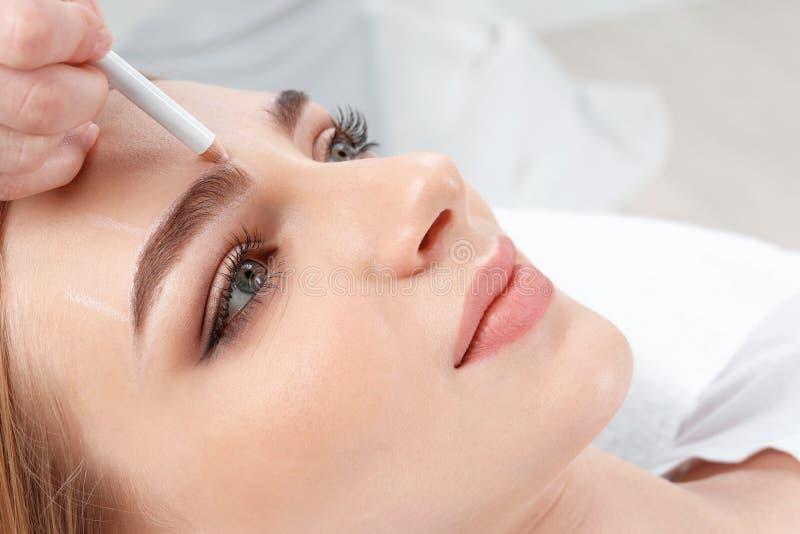 Cosmetologist som förbereder den unga kvinnan royaltyfri bild
