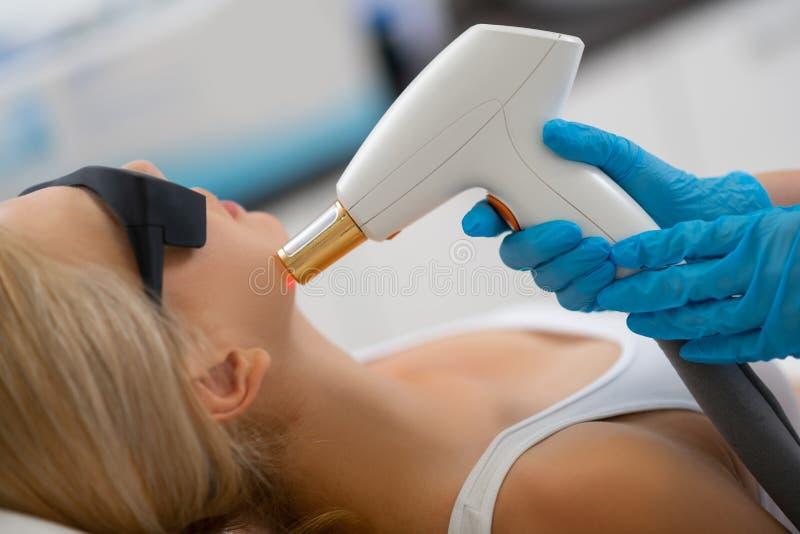 Cosmetologist som ger hennes klient laser-framsidabehandling royaltyfria foton