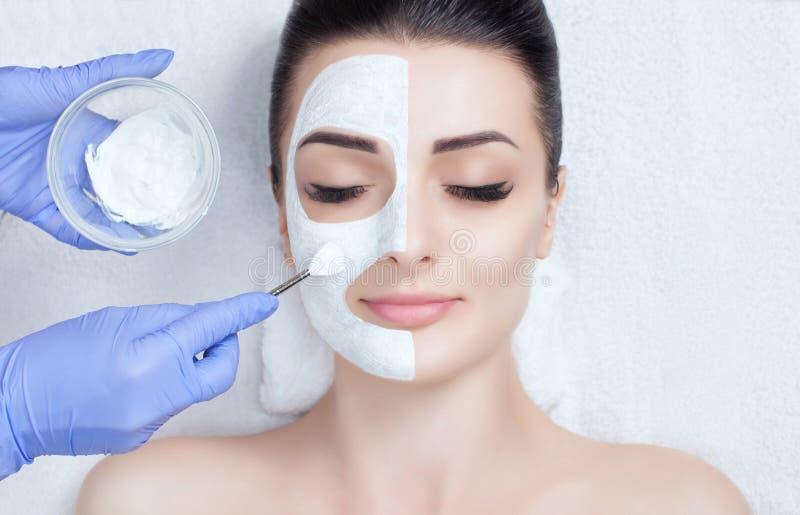 Cosmetologist voor de procedure die om de huid te reinigen en te bevochtigen, een masker met stok toepassen op het gezicht stock foto